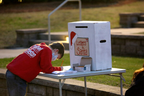 A masked Child dropping letters to Santa in a box prior to his arrival