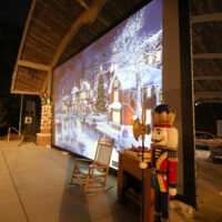 A large screen with an image of snow covered village. Also a rocking chair and nutcracker are present. Unknown on their intentions.