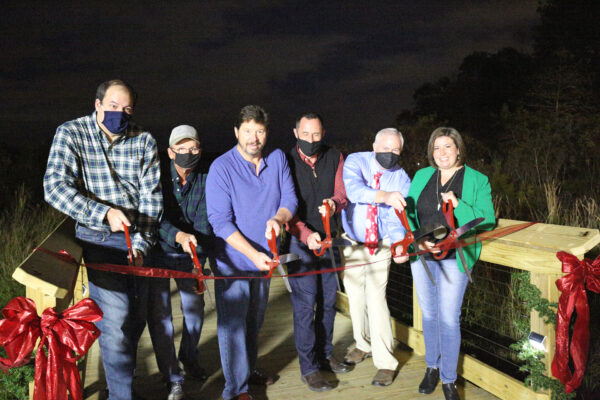 City Council Memebers holding oversized scissors preparing to cut a large red ribbon the open the new boardwalk.