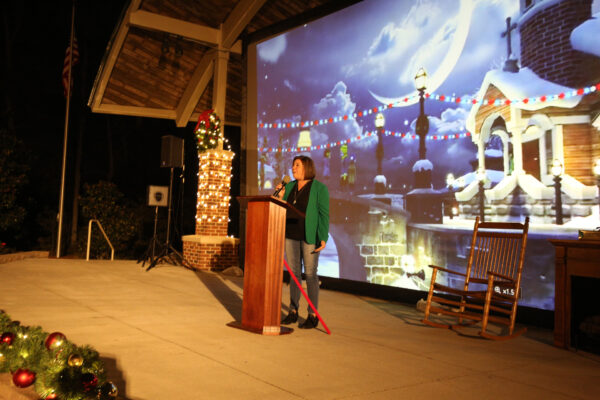 Mayor Rainwater speaking into a microphone with an image of a snowy building behind her