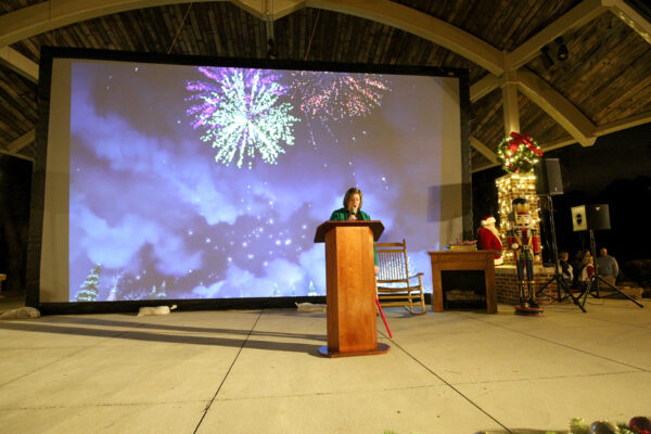 Mayor Rainwater speaking with emphasis into a microphone with an image of fireworks in the background