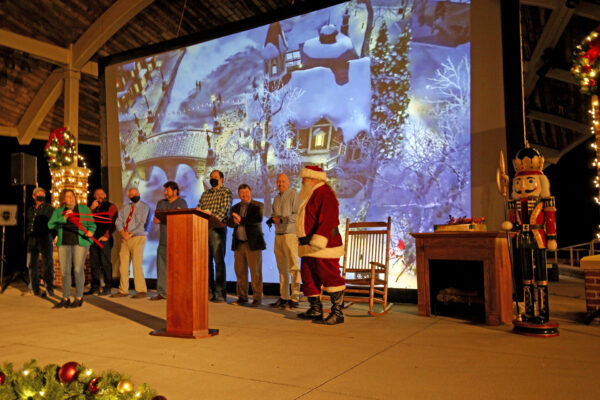 City Council Members, plus Dan Owens, and Santa standing in front of a large image of a snowy cabin