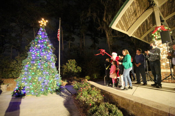 Santa, the Mayor, and some children looking at lighted Christmas Tree and smiling