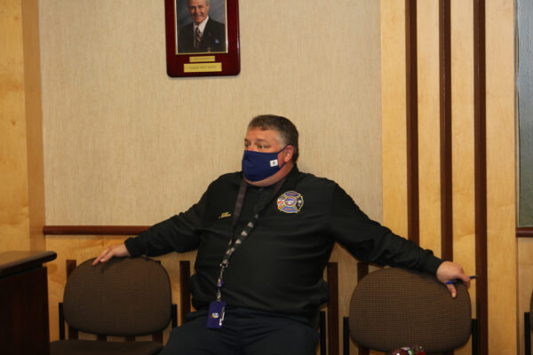 Fire Chief Bowers sitting in a chair looking at......something