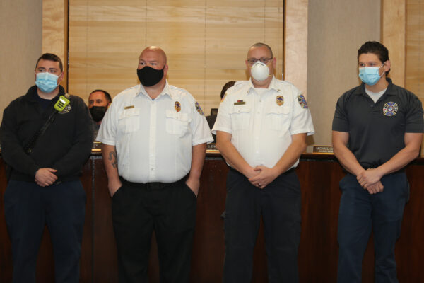 Four firefighters wearing masks and standing respectfully watching a speaker off camera