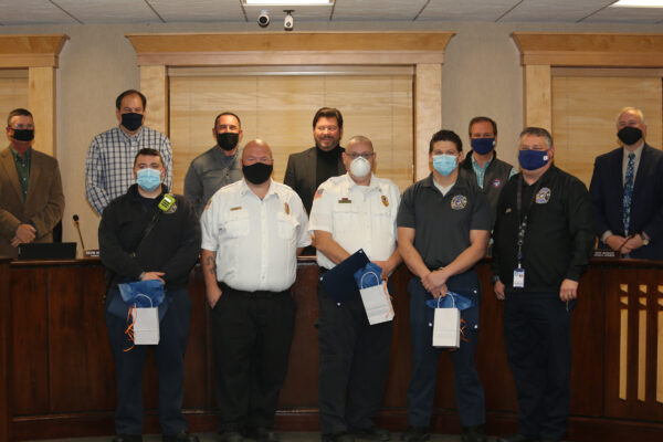 Four firefighters wearing masks and standing respectfully while Council members pose behind them.
