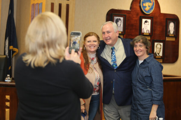 Councilman Boggs standing for photos with fans and or family members after being sworn in as a Councilman
